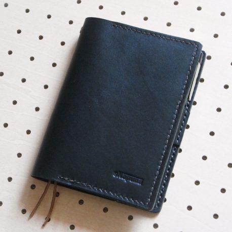 ほぼ日手帳カバー(A6文庫)商品画像000:ほぼ日手帳用のカバーですが、A6サイズのノートも収納可能です。ペンケースが内部に収納されるようになっています。見開き左にポケットがあり、A4の四折りメモや名刺などを収納できます。