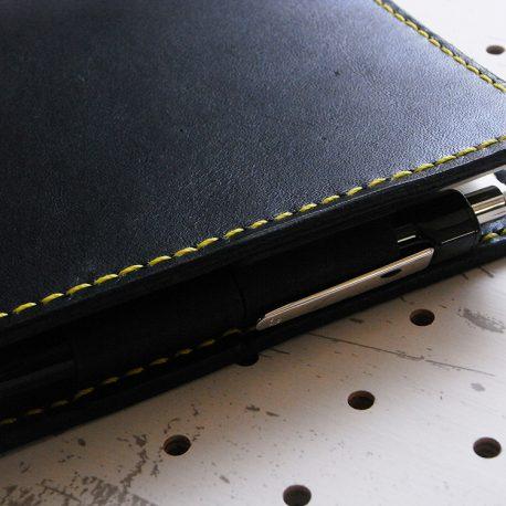 ノートカバー(B6)商品画像008:ペンケースのアップ画像です。バタフライストッパーが内側に配置している為、ペンが収まっています。